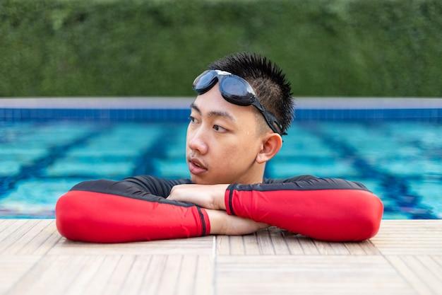 스포츠 및 레크리에이션 개념 수영장 가장자리에서 잡고 포즈를 취하여 연습으로 수영을 쉬고 있는 남성 청소년.