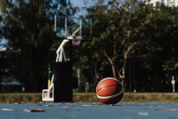 스포츠 및 레크리에이션 개념 농구 코트 바닥에 누워 있는 둥근 농구.