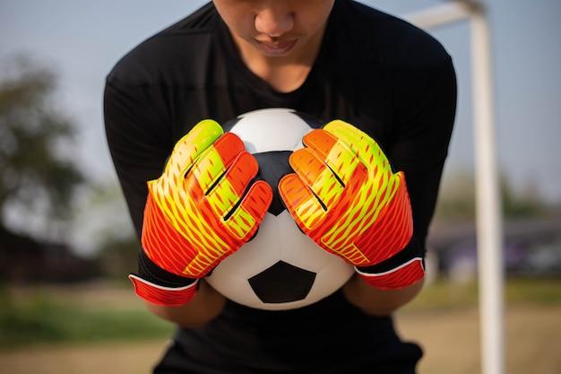 스포츠 및 레크리에이션 개념 젊은 남성 골키퍼는 양손으로 공을 잡고 상대 팀이 득점하는 것을 막습니다.