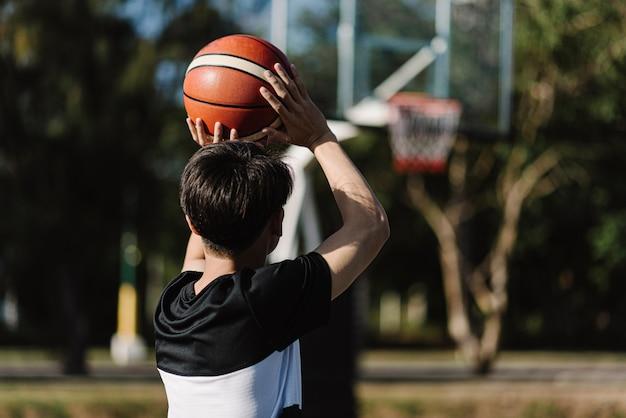 스포츠 및 레크리에이션 개념 방과 후 법원에서 농구공을 별도로 쏘는 연습을 하는 젊은 남성 10대.