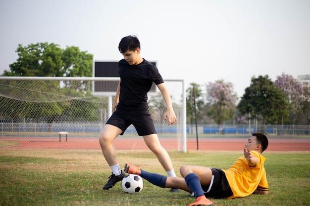 スポーツとレクリエーションのコンセプトは、定期的な練習セッションに参加し、攻撃と防御のパターンを記憶している2人の男性サッカー選手です。