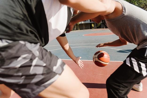 스포츠 및 레크리에이션 개념 방과 후 코트에서 드리블 농구를 연습하는 젊은 남성 십대.