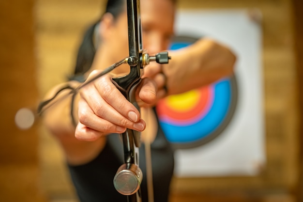 Sports archery woman at the shooting range, competition for the most points to win the cup