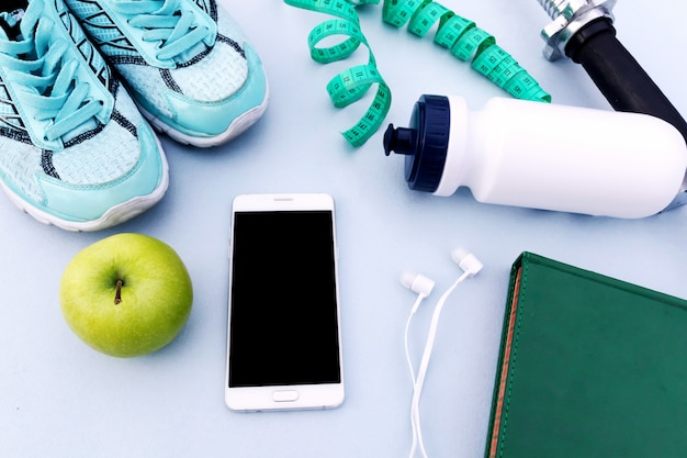 Sports background, sneakers, dumbbell, water, smartphone.