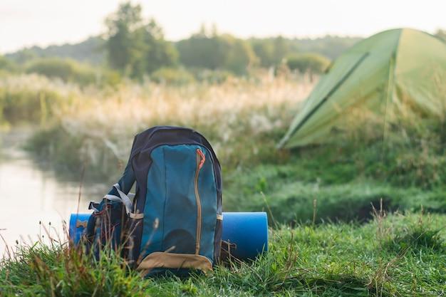 자연과 숲의 배경에 관광 텐트에 대한 깔개와 스포츠 배낭.