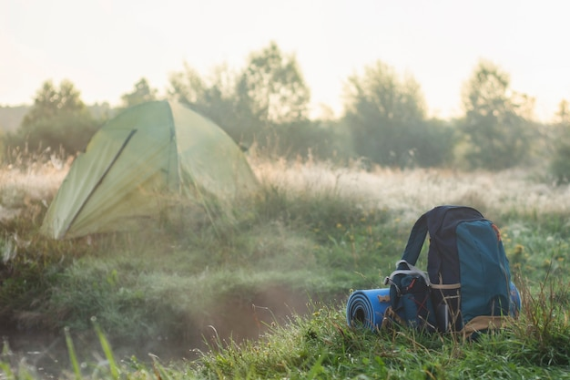 Sports backpack with a rug near a tourist tent on the background of nature and forest.