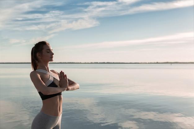 Mette in mostra la bella donna alla meditazione della spiaggia.