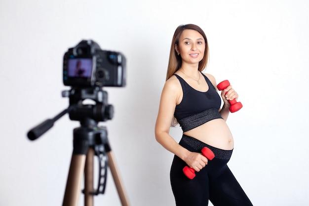 スポーツブロガー美しい妊婦がスポーツをし、カメラでトレーニングを撮影します