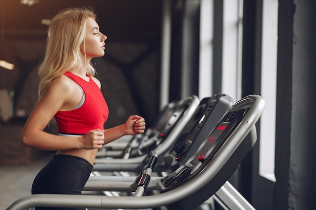 Sports blonde woman in a sportswear training in a gym
