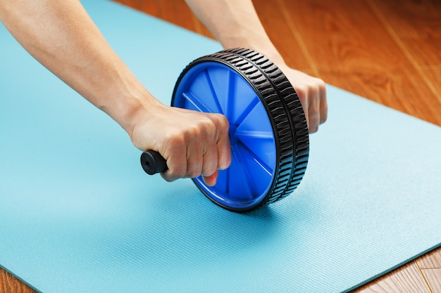 Sports blue roll for training the abs in the hands.