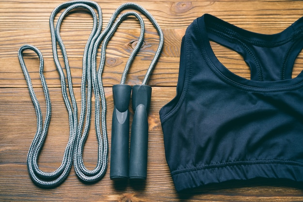 Sports bra and jump rope on wooden background