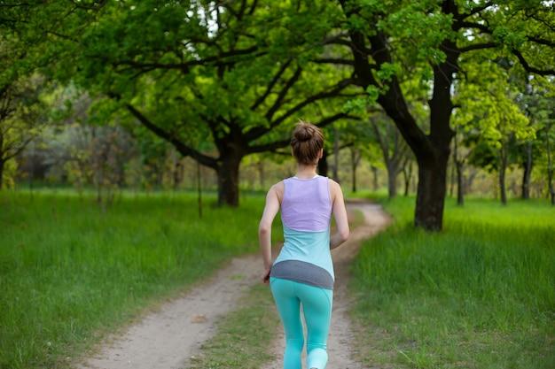 Sports brunette girl jogging in the park. green forest