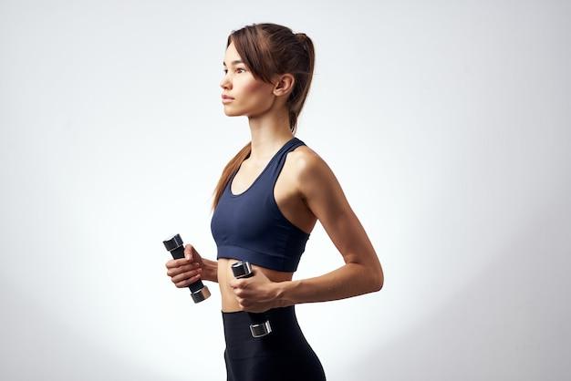 Спортивная брюнетка с гантелями в руках, тренировки фитнеса
