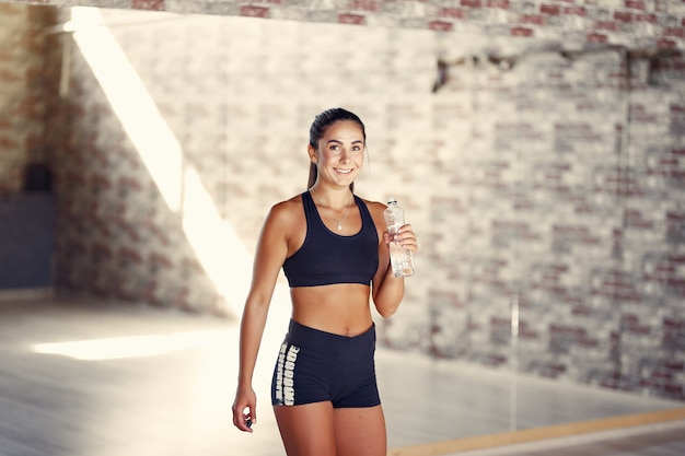 Sports brunette woman in a sportswear standing with a bootle