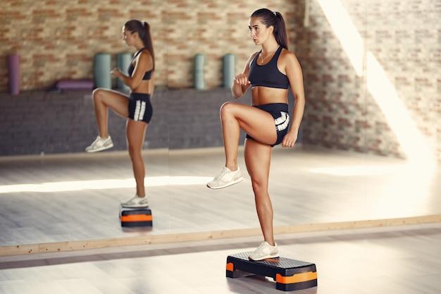 Sports brunette woman in a sportswear training in a gym