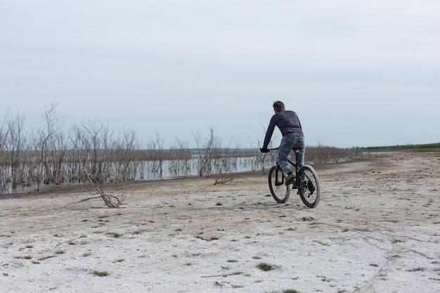 현대 산악 자전거를 탄 스포츠 잔인한 수염 난 남자. 호수 옆 소금기가 있는 황량한 장소에서 자전거를 타는 사람.
