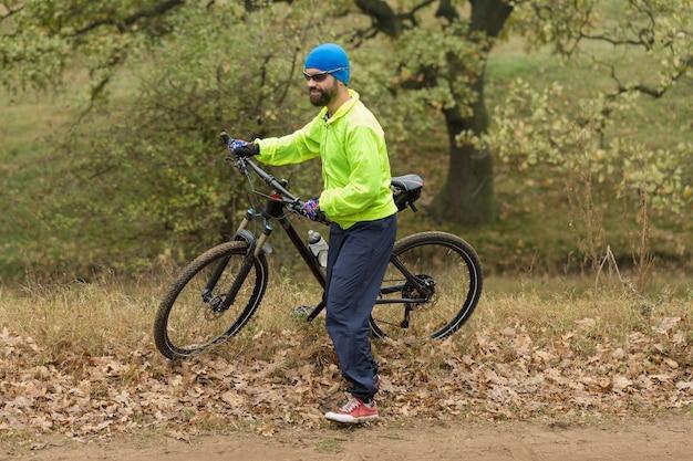 현대 산악 자전거에 스포츠 잔인한 수염 난 남자 산에서 아름다운 전망
