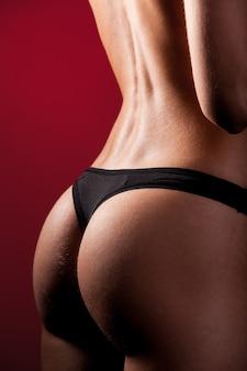 Спортивные ягодицы с мускулами и загорелой кожей девушки в черном нижнем белье