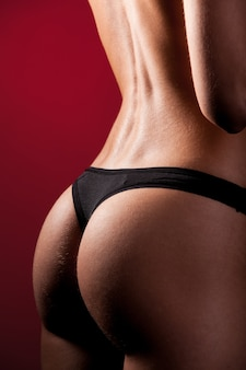 Sports buttocks with muscles and tanned skin of girl in black underwear