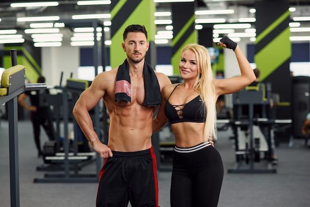 운동 후 체육관에서 스포츠 커플 포즈. 한 젊은 남자가 허리에 그의 여자 친구를 안았습니다.