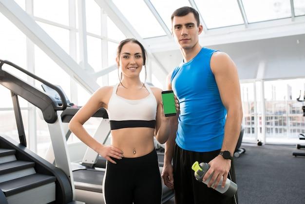 モバイルアプリを提示するスポーツカップル