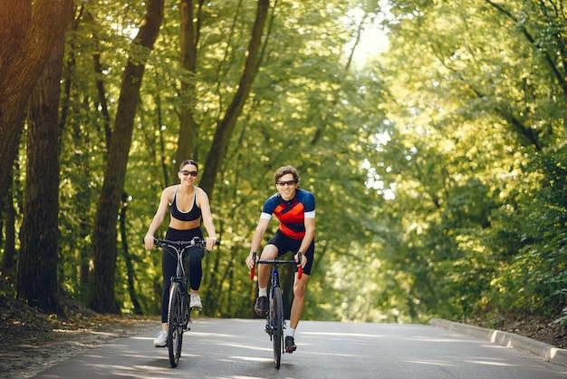 여름 숲에서 자전거를 타고 스포츠 커플