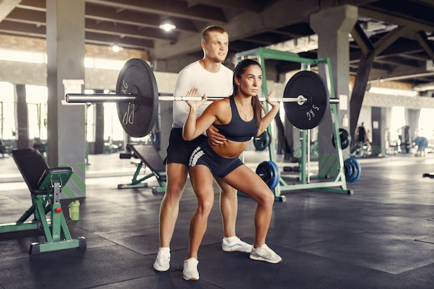 Sports couple in a sportswear training in a gym
