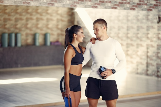 Sports couple in a sportswear training in a gym