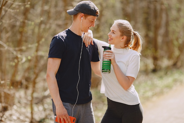 Sports couple training in a summer forest