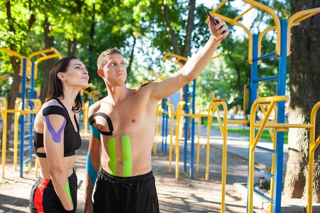 야외에서 셀카를 찍는 운동학적 테이핑을 한 스포츠 커플.
