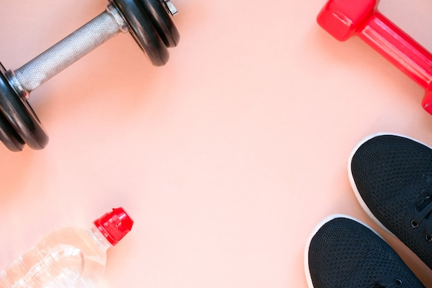 Sports crafts, dumbbells, drinking water on pink background