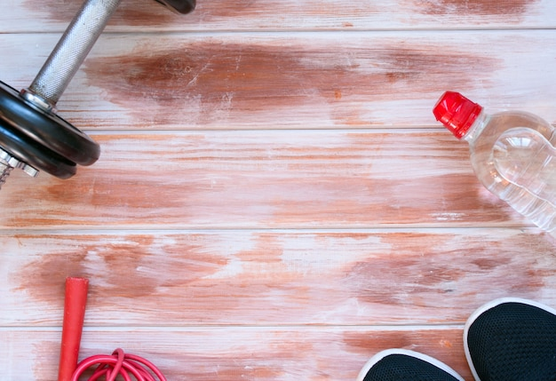 Sports crafts, dumbbells, drinking water on wooden background