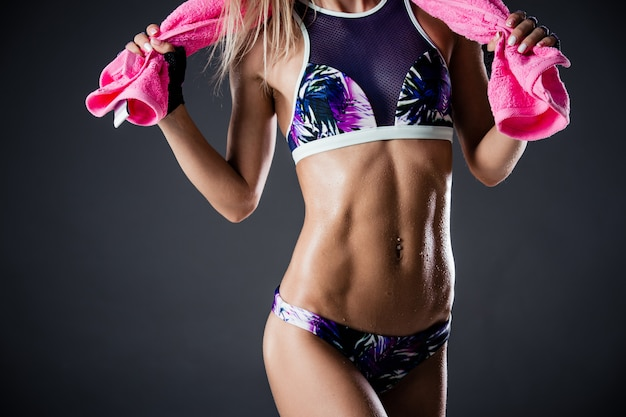 Sports dehydration. cropped closeup of a stunning fitness woman at studio on dark