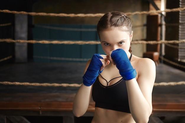 スポーツ、決意、フィットネス、格闘技。黒のドライフィットトップと防御姿勢で立っているボクシングの包帯を身に着けているスポーティな女の子、