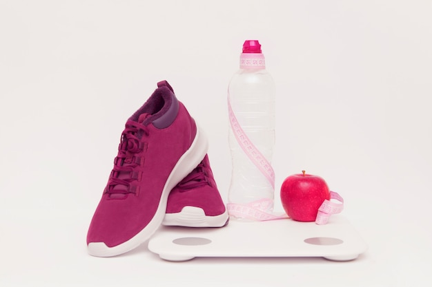 Sports equipment, apple and scales a bottle water on a toned background.