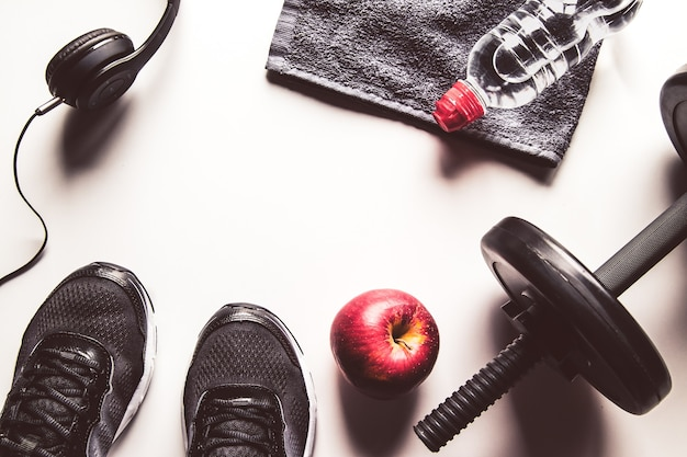 Sports equipment, apple and water bottle
