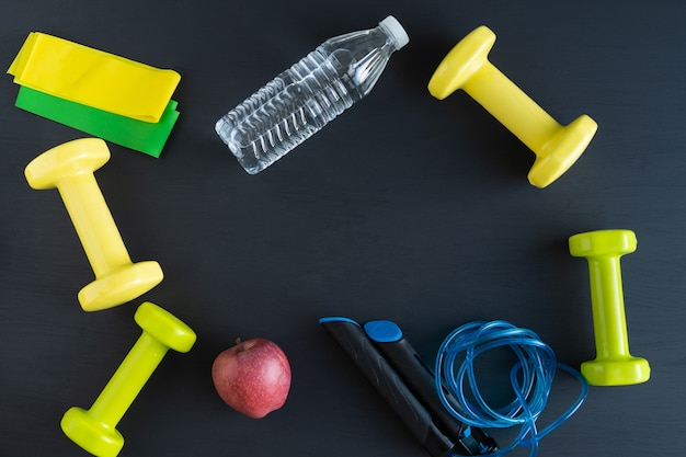 Sports equipment on black background for exercising at home. copy space.