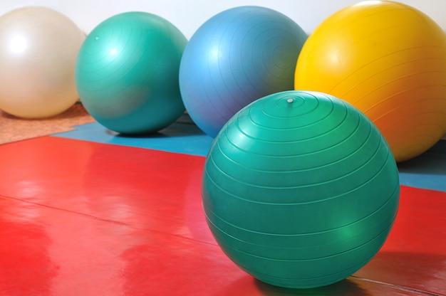 Рядом находится спортивный инвентарь, мячи для фитнеса и спортивные принадлежности разного цвета.