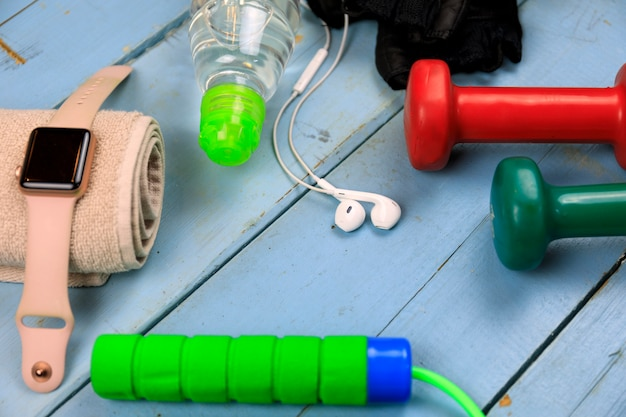 Sports equipment for fitness training. bottle with water, smart watch, earphones and jumping-rope. set for sports activities.