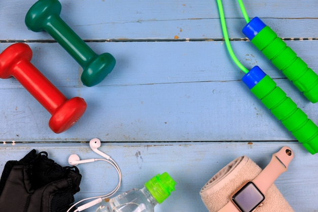 Sports equipment for fitness training on a wooden background.