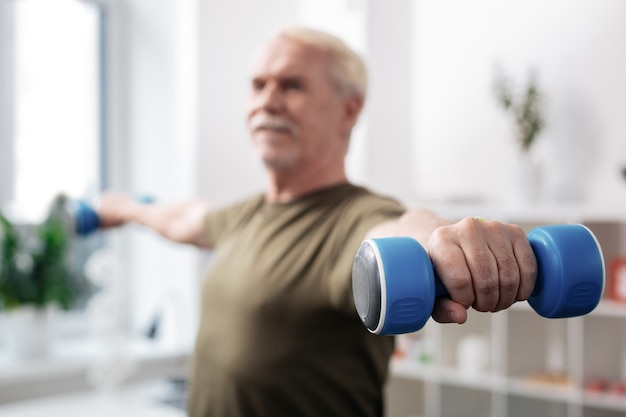 Sports equipment. selective focus of a dumbbell in a male hand during the workout