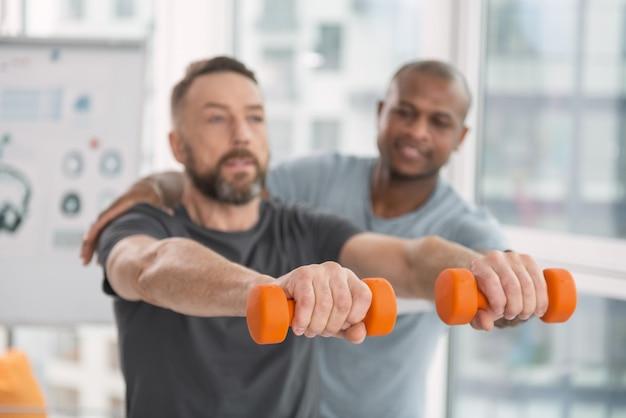 スポーツ用品。オレンジ色のダンベルの選択的な焦点