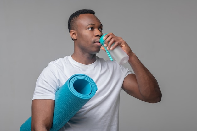 Sports equipment. serious young adult african american with blue sports mat standing drinking water from special bottle