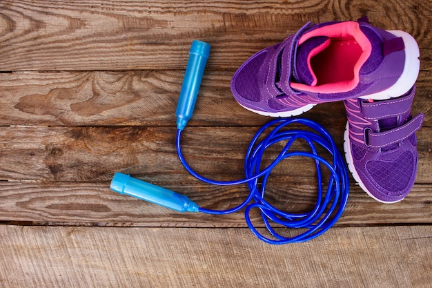 Sports equipment: skipping rope and sneakers on wooden background