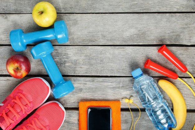 Sports equipment and the smartphone with earphones on a wooden
