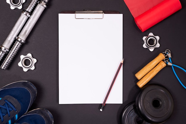 Sports equipment for sports and fitness, top view, black background, in the middle a paper holder with empty white sheets