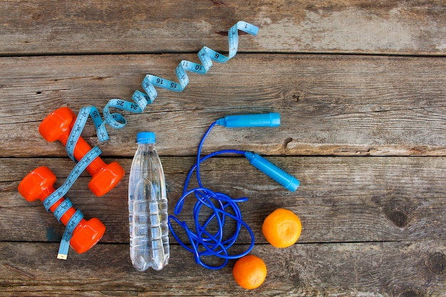 Sports equipment, water and tangerines in top view