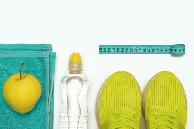 Sports equipment on a white toned background, top view. the  healthy lifestyle, healthy food, sports and diet.