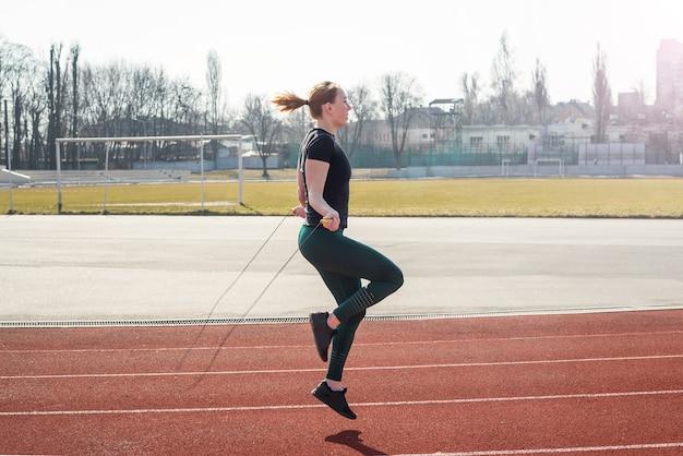 スポーツ、自然の中での運動。スタジアムで縄跳びをする女性。