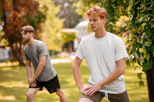 스포츠 운동입니다. 따뜻하고 화창한 아침에 야외에서 격렬하게 운동을 하는 운동복을 입은 두 명의 집중된 운동 선수